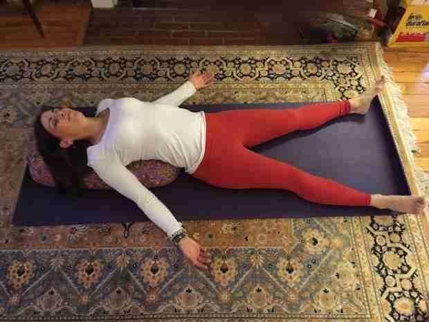 Restorative back bend over a yoga bolster